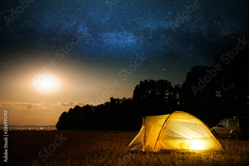 Traveling and camping concept - camp tent at night under a sky full of stars. Orange illuminated tent and car. Beautiful nature - field, forest, plain. Moon and moonlight