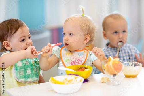 Fotografia  kids children babies eating healthy food in kindergarten or at daycare