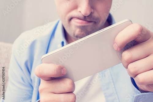 A young man uses a smartphone, a man with passion playing games with a mobile ph Canvas Print