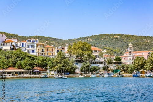 Photo boats on the body of water surrounded by trees and houses in Skiathos, Greece un