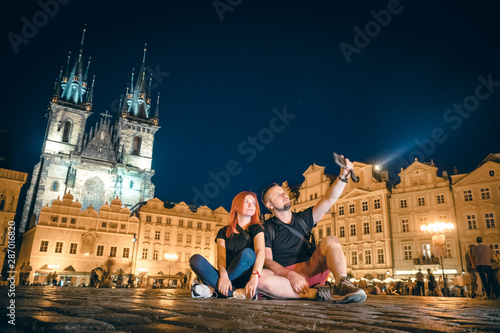 Loving couple sit in the main square, taking pictures on the phone, selfie smartphone, happy together, on the street of the old city of Prague, night time Canvas Print