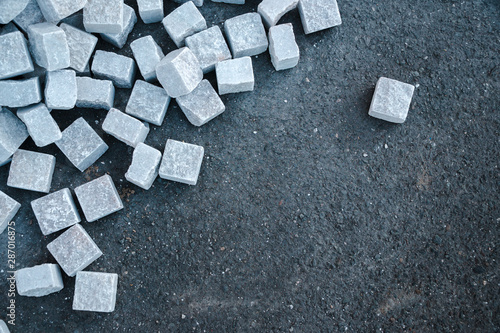 Obraz Top view. stone cube pavement, construction worker laying cobblestone rocks on sand, tile stacker, road works, sidewalk reconstruction, decorative for the garden. texture background, copy space - fototapety do salonu