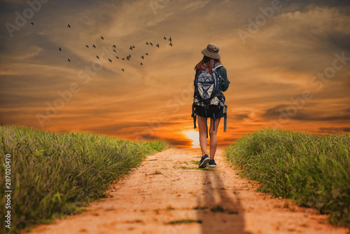 Foto auf AluDibond Gras Alone young girl walking on the dirt road.