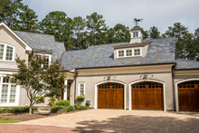 Stained Wood Triple Custom Garage Doors For Large Southern Home With Curb Appeal