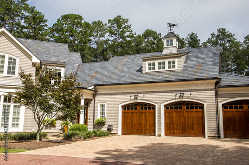 Fotografia, Obraz Stained wood triple custom garage doors for large southern home with curb appeal