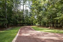 Long Gravel Driveway Which Leads To A House Secluded In Trees