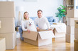 Young beautiful couple with dog sitting on the floor at new home around cardboard boxes