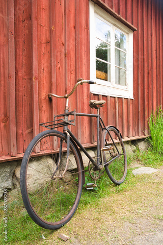 Türaufkleber Fahrrad Old bicycle leaning against wooden wall of a house