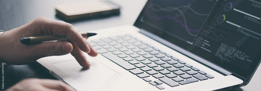 Fototapeta Businessman is using laptop and analysing the financial information at his office. Close up of male hands typing on computer keyboard