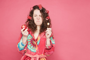 .Close up shot of grimacing housewife in colorful bathrobe feeling disgust to eat healthy organic apple or unhealthy candy, dislike to keep diet, isolated on pink studio wall with copy space.