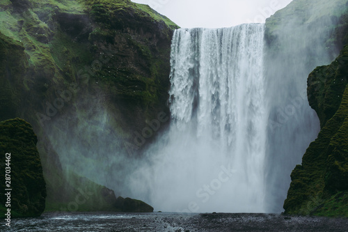 Majestic Skogarfoss waterfall in Iceland. White and green splashes flying all around against green hills covered with moss. - 287034462