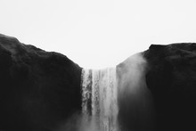Falling Water Of Skogarfoss Waterfall Between Green Hills In Iceland. Gray Cloudy Sky And White Splashes. Gothic Black And White Tones.