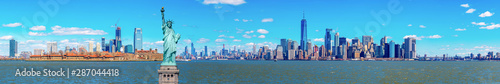 Poster Bleu Panorama of The Statue of Liberty with the One world Trade building center over hudson river and New York cityscape background, Landmarks of lower manhattan New York city.