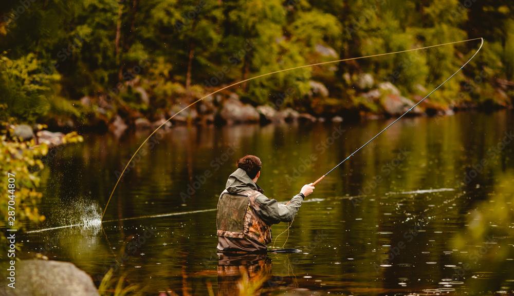 Fototapeta Fisherman using rod fly fishing in mountain river