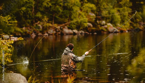 Leinwand Poster Fisherman using rod fly fishing in mountain river