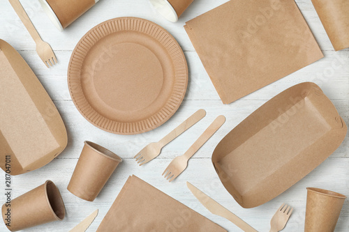 Fotografía  Flat lay composition with new paper dishware on white wooden background