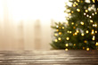 canvas print picture Empty table and blurred fir tree with yellow Christmas lights on background, bokeh effect. Space for design