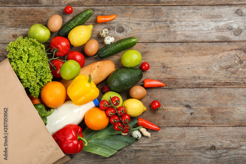 Poster Keuken Flat lay composition with overturned paper bag and groceries on wooden table. Space for text