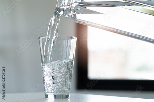 Fotografia  woman pouring down mineral water to glass.