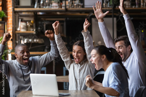 Stampa su Tela Euphoric diverse friends celebrating victory watching online game on laptop