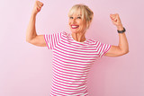 Middle age woman wearing striped t-shirt standing over isolated pink background showing arms muscles smiling proud. Fitness concept.