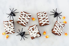 Halloween Mummy Brownies, Top View With Decor On A White Marble Background