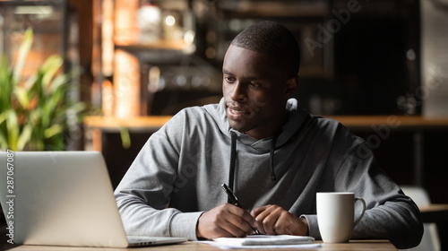 Fotografía  Focused young man studying with laptop make notes in cafe