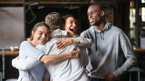 Excited diverse friends embrace greeting male buddy coming at meeting