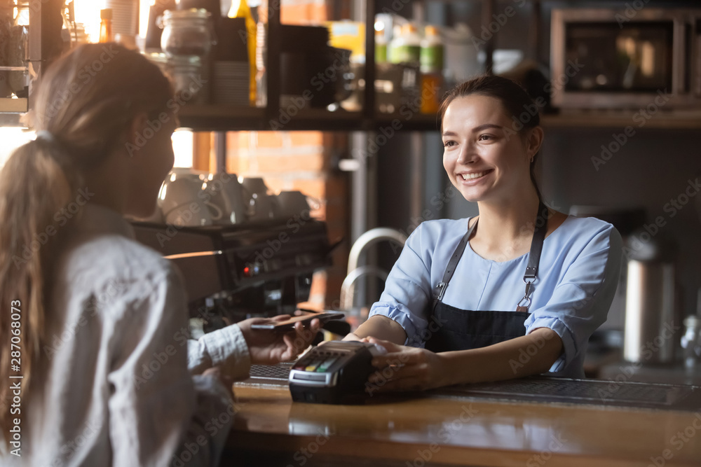 Fototapeta Female customer pay with phone on nfc with smiling barista