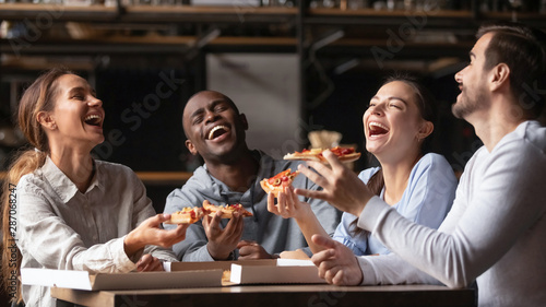 Happy diverse friends laughing at funny joke share pizza