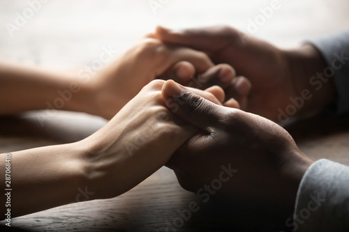 Obraz Mixed ethnicity couple holding hands on table, close up view - fototapety do salonu
