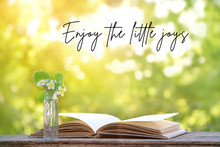 Enjoy The Little Joys - Inspiration Quote. Pretty  Flowers Of Strawberry And Open Book On Wooden Table, Summer Garden Scene. Gently Nature Composition. Shallow Depth, Soft Focus
