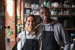 canvas print picture - Happy diverse waiter and waitress looking at camera in restaurant