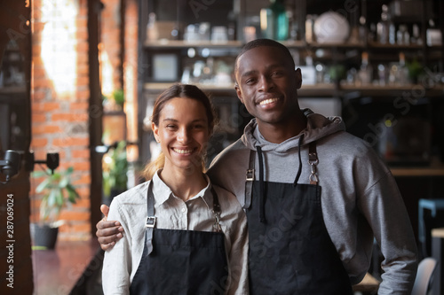 Happy diverse waiter and waitress looking at camera in restaurant