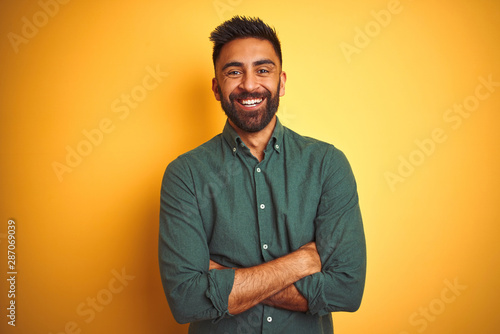 Fotografía  Young indian businessman wearing elegant shirt standing over isolated white background happy face smiling with crossed arms looking at the camera