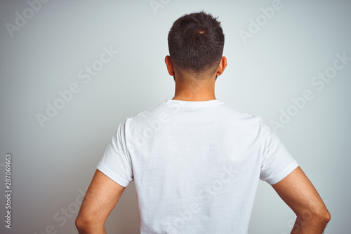 Young indian man wearing t-shirt standing over isolated white background standing backwards looking away with arms on body