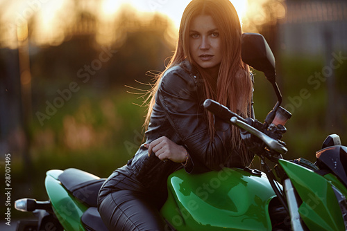 Beautiful young girl with a fashionable hairstyle and red lips poses next to motorcycle