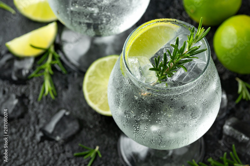 Foto Gin and Tonic Alcohol drink with Lime, Rosemary and ice on rustic black table