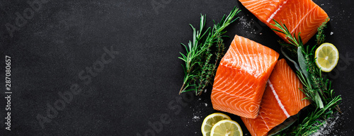 Fototapeta Salmon. Fresh raw salmon fish fillet with cooking ingredients, herbs and lemon on black background, top view, banner obraz