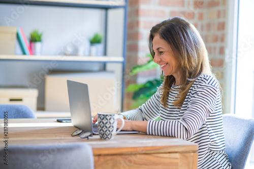 Middle age senior woman sitting at the table at home working using computer laptop with a happy face standing and smiling with a confident smile showing teeth