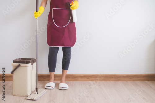 Fotomural  Close up view of body of young woman holding stuff for cleaner ready to cleaning house