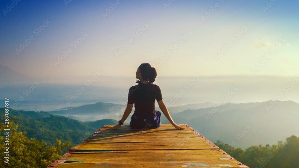 Fototapety, obrazy: Young woman sits and enjoys Ngisis hill view