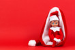 canvas print picture - Little smiling Christmas toy elf sitting in Santa hat on red background
