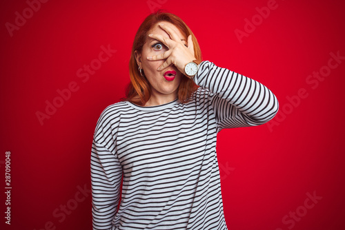 Fotomural  Young redhead woman wearing strapes navy shirt standing over red isolated background peeking in shock covering face and eyes with hand, looking through fingers with embarrassed expression