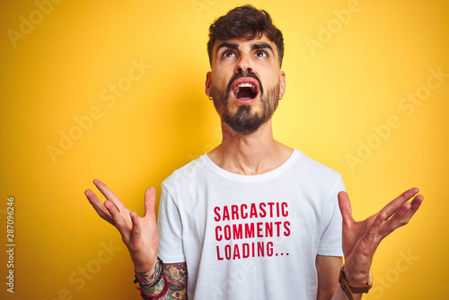 Obraz na plátně  Young man with tattoo wearing fanny t-shirt standing over isolated yellow background crazy and mad shouting and yelling with aggressive expression and arms raised