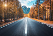 canvas print picture - Road in autumn forest at sunset in Italy. Beautiful mountain roadway, trees with orange foliage and sunlight. Landscape with empty asphalt road through woodland, blue sky, high rocks in fall. Travel
