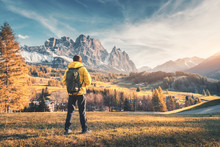 Young Man With Backpack Standing On The Hill Against The Mountains At Sunset In Autumn. Landscape With Sporty Guy, Meadow,  Snowy Rocks, Orange Trees, Houses, Blue Sky. Travel In Italy In Fall