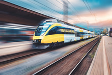 High Speed Yellow Train In Motion On The Railway Station At Sunset. Modern Intercity Passenger Train With Motion Blur Effect On The Railway Platform. Industrial. Railroad And Blurred Background