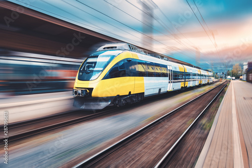 Fotografía  High speed yellow train in motion on the railway station at sunset