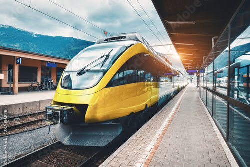 Photo  Beautiful high speed train on the railway station in mountains at sunset in autumn Yellow modern commuter train on the railway platform